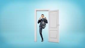 一个年轻商人在一个小被删去的门框站立并且踢门开放与他的脚 免版税库存图片