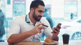 一个年轻商人在café使用与巧妙的电话的网路银行,当坐和有早餐购买在时 股票视频