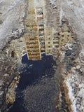 一个水坑,在熔化雪边缘与有点大黄色前面,水的蓝色表面的被倒置的反射的和 免版税库存图片