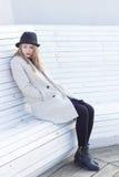 一个黑外套和帽子的孤独的哀伤的美丽的女孩,坐一个白色长凳冷的冬天晴天 免版税库存图片