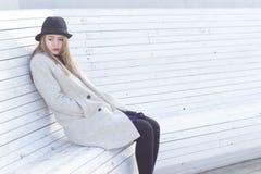 一个黑外套和帽子的孤独的哀伤的美丽的女孩,坐一个白色长凳冷的冬天晴天 免版税库存照片