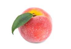 一个水多的桃红色桃子的特写镜头与在白色背景隔绝的一片绿色叶子的 充分成熟和健康桃子维生素 免版税图库摄影