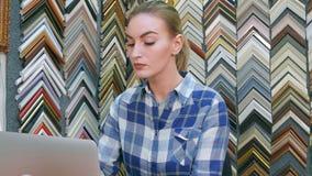 一个年轻女性企业主的画象在柜台后的使用便携式计算机在她的商店 免版税库存照片
