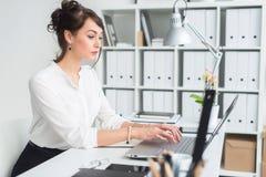 一个年轻女性办公室工作者的画象在键入她的工作场所,看坐膝上型计算机屏幕殷勤地 图库摄影
