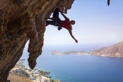 一个年轻女性攀岩运动员的剪影峭壁的 库存照片