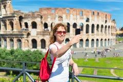 一个年轻女性游人的Selfie Coloss的背景的 库存图片