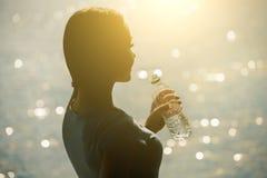 一个年轻女运动员的剪影田径服饮用水的从在海滩的一个瓶在夏天早晨行使 免版税库存照片