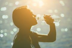 一个年轻女运动员的剪影田径服饮用水的从在海滩的一个瓶在夏天早晨行使 免版税图库摄影