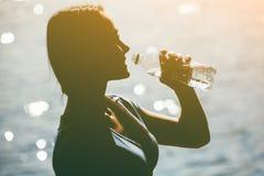 一个年轻女运动员的剪影田径服饮用水的从在海滩的一个瓶在夏天,早晨行使 免版税库存图片