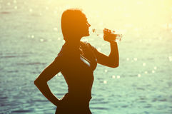一个年轻女运动员的剪影田径服饮用水的从在海滩的一个瓶在夏天, 免版税库存照片