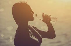 一个年轻女运动员的剪影田径服饮用水的从瓶 免版税图库摄影