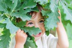 一个婴孩的画象绿色叶子的 迷住,快乐的微笑的孩子 库存图片