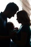 一个年轻家庭的剪影有孩子的窗口的 图库摄影