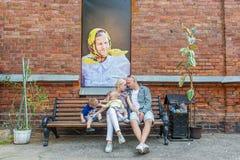 一个年轻家庭的画象对有图片的背景红砖墙壁 免版税库存照片