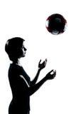 一个年轻少年扔足球橄榄球的女孩剪影 免版税库存图片