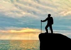 一个登山人的剪影在上面的在远处看海 免版税库存照片