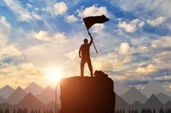 一个登山人的剪影在山上面的 库存图片