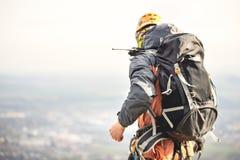 一个登山人的特写镜头从后面的在齿轮和有一个背包的用在传送带的设备,在一个岩石的立场,在上流 库存图片