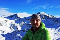 一个年轻登山人的画象在一个峰顶在Retezat山,罗马尼亚顶部的 免版税库存图片