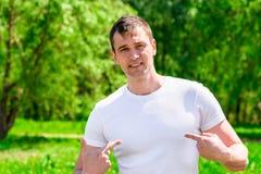 一个35岁的人的画象在一个绿色公园的背景中 免版税库存照片