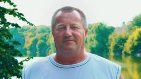 一个50岁的胖的人的画象反对自然` s绿叶背景的,一个成人捷径人站立与他的 股票视频