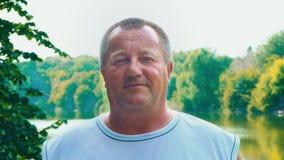 一个50岁的胖的人的画象反对自然` s绿叶背景的,一个成人捷径人站立与他的 影视素材