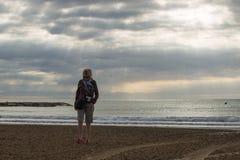 一个离开的海滩的妇女 库存照片