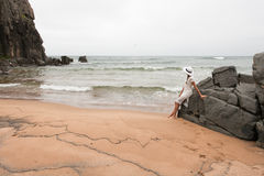 一个离开的海滩的孤独的苗条妇女在大石头和多云天空背景  免版税库存图片