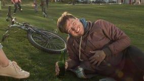 一个年轻微笑的人在公园在有一个瓶的草坪说谎在他的手上 愉快的人在有朋友的一个公园休息 股票录像