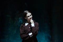 一个年轻微笑的女孩的画象校服的当凶手妇女 免版税库存图片