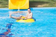 一个年轻快乐的人获得乐趣在度假在水池在水公园 库存照片
