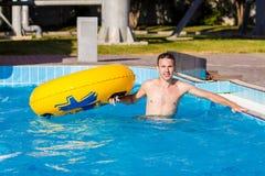 一个年轻快乐的人获得乐趣在度假在水池在水公园 免版税库存图片