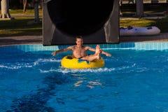 一个年轻快乐的人获得乐趣在度假在水池在水公园 免版税库存照片
