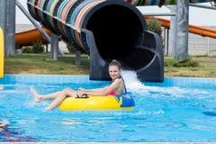 一个年轻快乐的女孩获得乐趣在度假在一个游泳池在水公园 免版税库存图片
