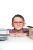 一个年轻愉快的男孩的画象红色眼镜的与书。 免版税库存照片