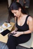 一个年轻拉丁女性文字正文消息的画象在她的手机的在咖啡休息期间在户外餐馆 免版税库存照片