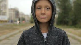 一个黑敞篷的一个男孩在街道上 股票录像