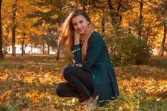 一个黑斗篷的年轻逗人喜爱的女孩在公园在秋天坐草坪并且微笑 免版税库存照片