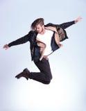 一个年轻时尚人的侧视图皮夹克跳跃的 库存照片