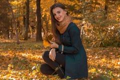 一个黑暗的斗篷的逗人喜爱的女孩在秋天公园坐保留叶子和微笑 免版税库存照片