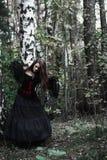 一个黑暗的森林美丽的少妇的万圣夜巫婆巫婆服装的 万圣夜艺术设计 恐怖背景为万圣夜 图库摄影