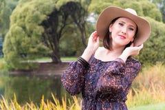 一个黑暗的礼服和白色帽子的一个少妇 免版税库存照片