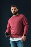 一个年轻有胡子的英俊的行家人,打扮在有长的袖子和牛仔裤的一件红色套头衫,站立户内 库存图片