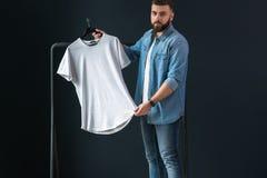 一个年轻有胡子的行家人在牛仔布衬衣,立场穿戴了户内反对背景 免版税库存图片