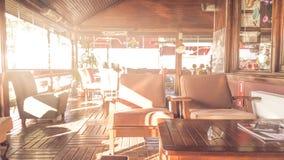 一个晴朗的空的夏天咖啡大阳台的软性彩色照片与桌和轻松的位子的 库存照片