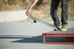 一个滑板的一个年轻人在一skatepark的一个指南在房子背景  免版税图库摄影