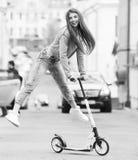 一个滑板的女孩在城市 图库摄影