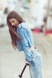 一个滑板的女孩在城市 免版税库存照片