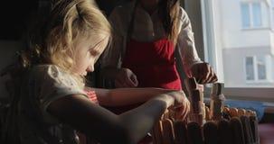 一个年轻母亲和她的小女儿装饰生日蛋糕 影视素材