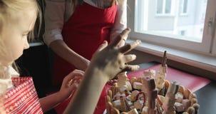 一个年轻母亲和她的小女儿装饰生日蛋糕 股票录像